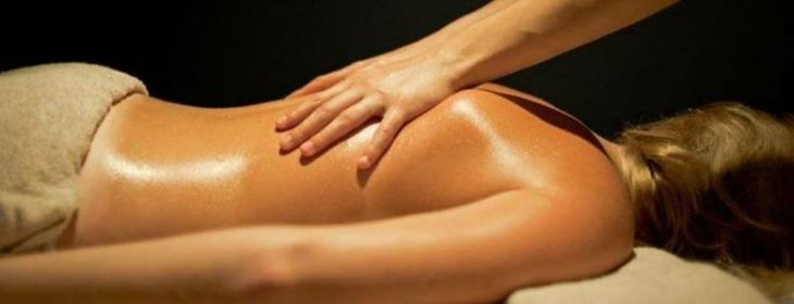 Femme allongée sur le ventre qui reçoit un massage aux huiles